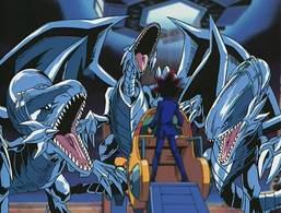 "Yami Yugi standing before three ""Blue-Eyes White Dragons"""